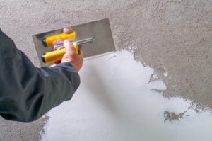 Construction worker - plastering and smoothing concrete wall wit
